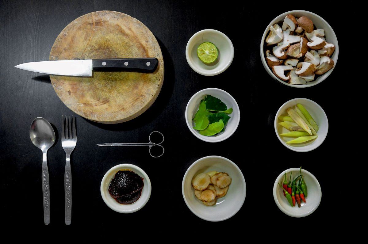 Black background with 6 white bowls with various ingredients, starting from the top lime, portobello mushrooms, green leaves, lemon grass, shiitake mushrooms, thai chilis, the 7th bowl set off to the side has a dark paste, then above that are scissors, left of the paste are a fork and spoon and above the scissors is a round wooden cutting board with a black handed chef knife laid over the top