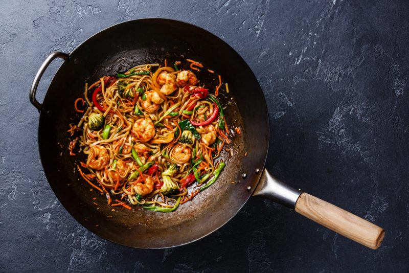 A frying pan of a spicy Asian meal on a table