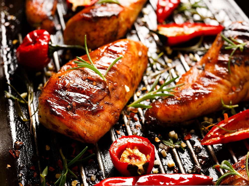 Pieces of marinated grilled chicken on a BBQ with herbs and peppers