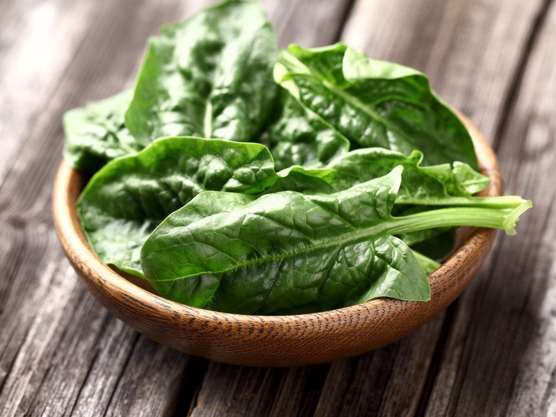 A wooden dish filled with spinach leaves rests on a rustic wooden tabletop.