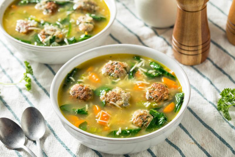 Spinach and meatball soup served in white bowls on a table cloth