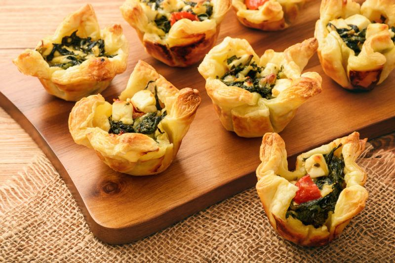 A collection of filo pastry apptetizers containin spinach