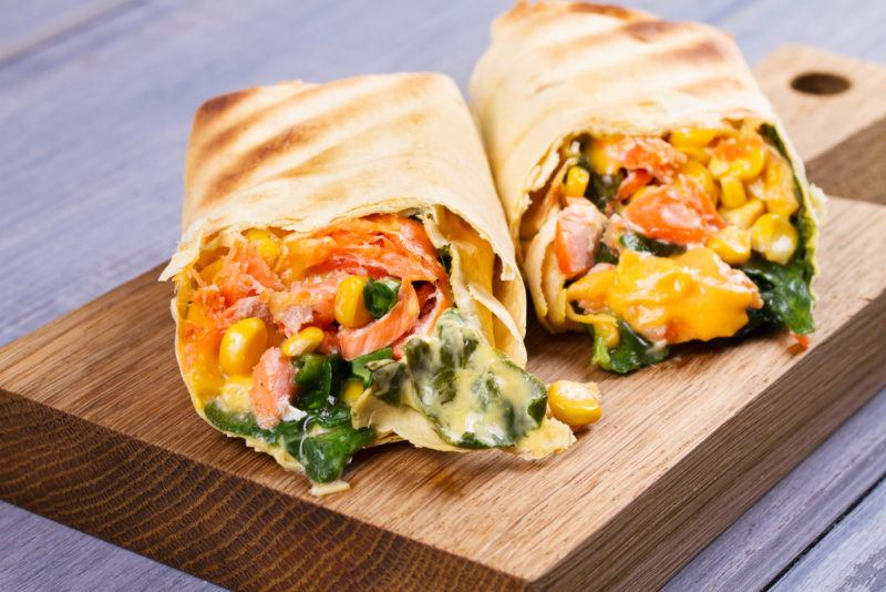 Breakfast burritos that contain spinach, salmon and a collection of other ingredients