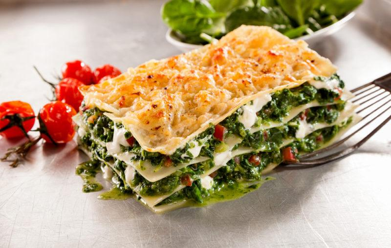 Lasagna that uses spinach and no meat on a white plate