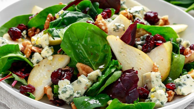 A salad containing spinach, pear, nuts and blue cheese