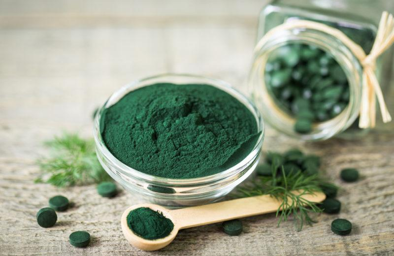 A glass bowl of spirulina, with a spoon and a glass jar containing spirulina tablets