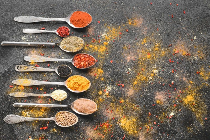 Spoons with spices on a black background