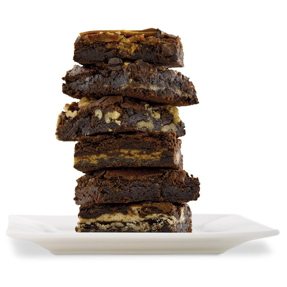 Stack of 6 brownies on a white square plate.  Flavors featured are chocolate, chocolate walnut, cookies and cream, and double chocolate