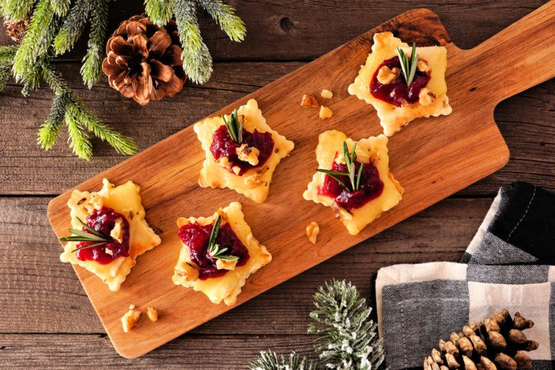 A wooden board with star shaped Christmass appetizers that use cranberry and brie as key ingredients