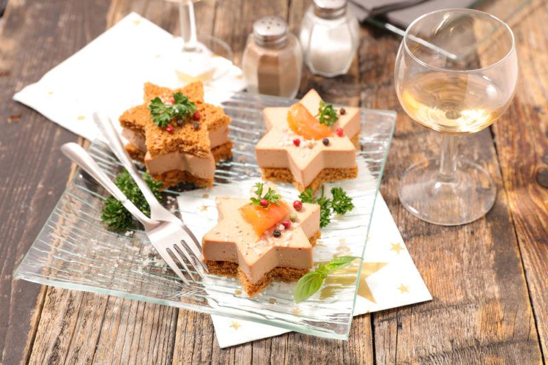 Three pieces of star shaped foie gras on a wooden table with sauternes wine