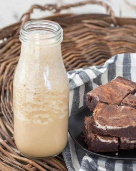 A cream-based drink in a bottle next to brownies