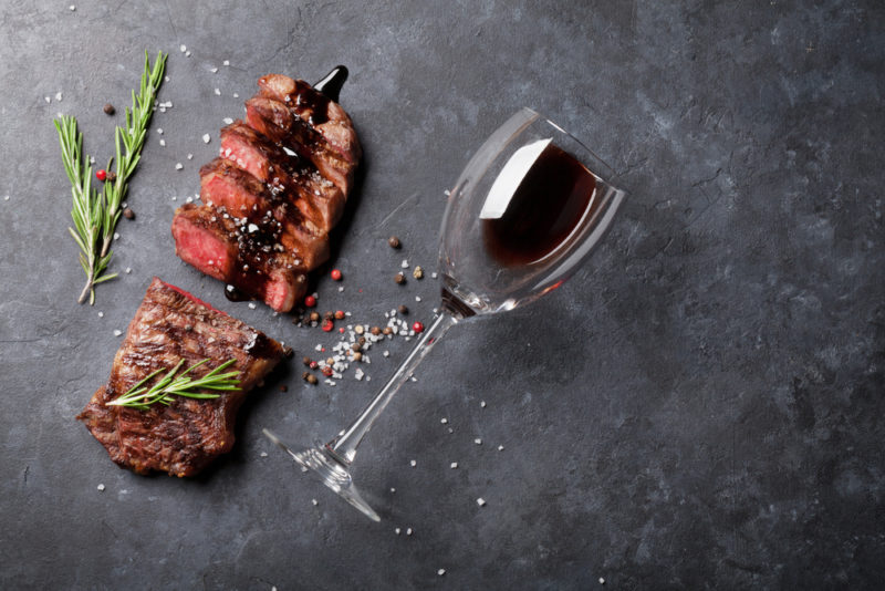 A slate tabletop on which there is steak and a glass of red wine lying down