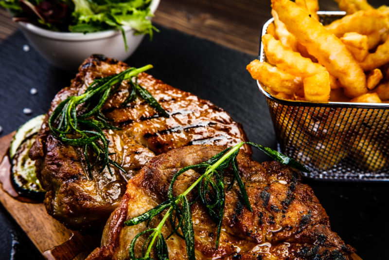 A wooden board with cooked steak, next to fries
