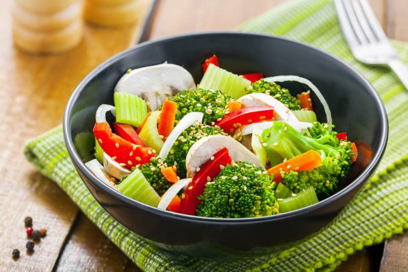 A black bowl with steamed veggies
