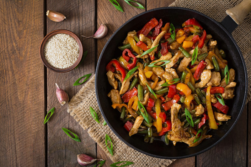 A black frypan on a wooden table that contains a fresh stirfry with peppers and other ingredients