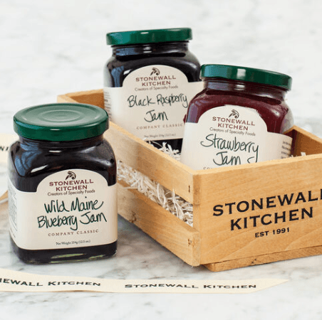 Three Stonewall Kitchen square jars of jam Wild Maine Blueberry, Black Raspberry, and Strawberry.  Two are set in a small wooden crate with raffia packing.  A ribbon is featured at the bottom with Stonewall Kitchen stamped on it.