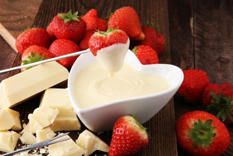 A heart shaped white container of white chocolate, with white chocolate and strawberries around it. One strawberry is being dipped into the chocolate.