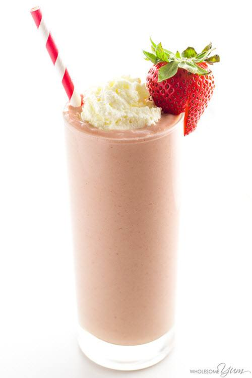 A strawberry smoothie in a glass against a white background