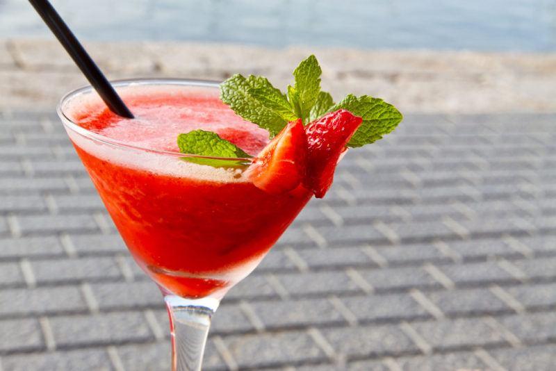 A strawberry daiquiri on a beach