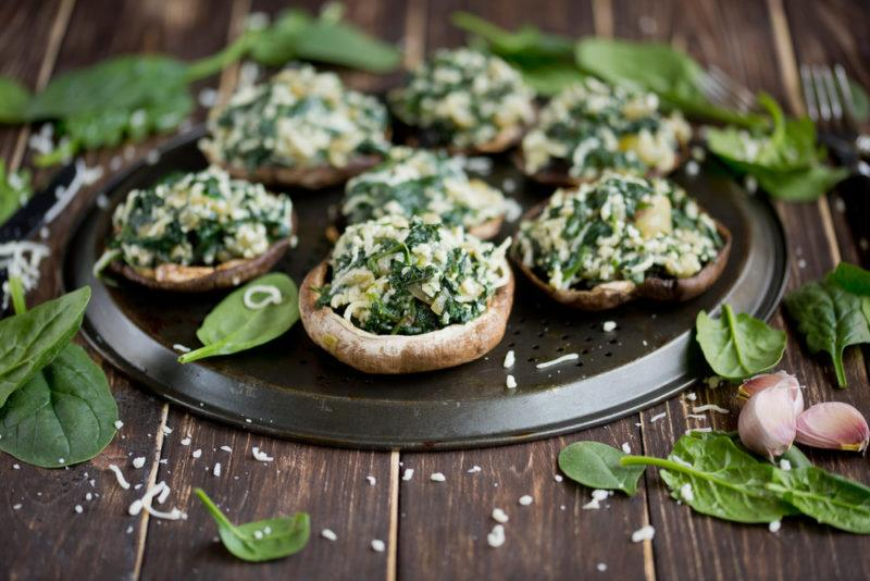 A selection of vegan stuffed mushrooms on a plate that's on a wooden table