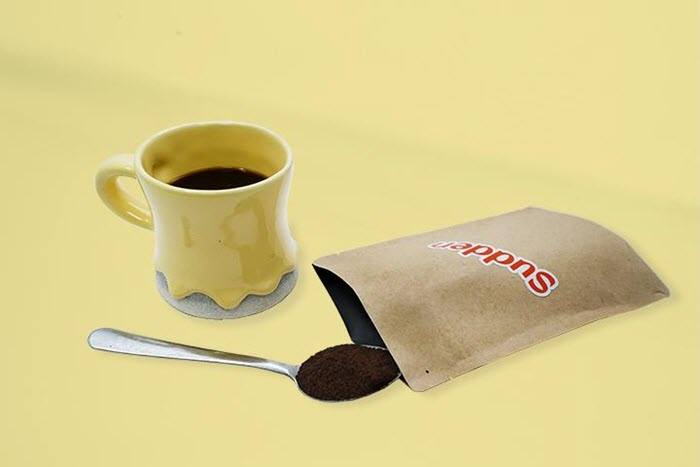 A sachet of coffee with a cup