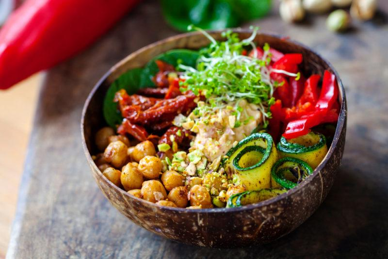 A brown bowl with sundried tomatoes, zucchini, and chickpeas