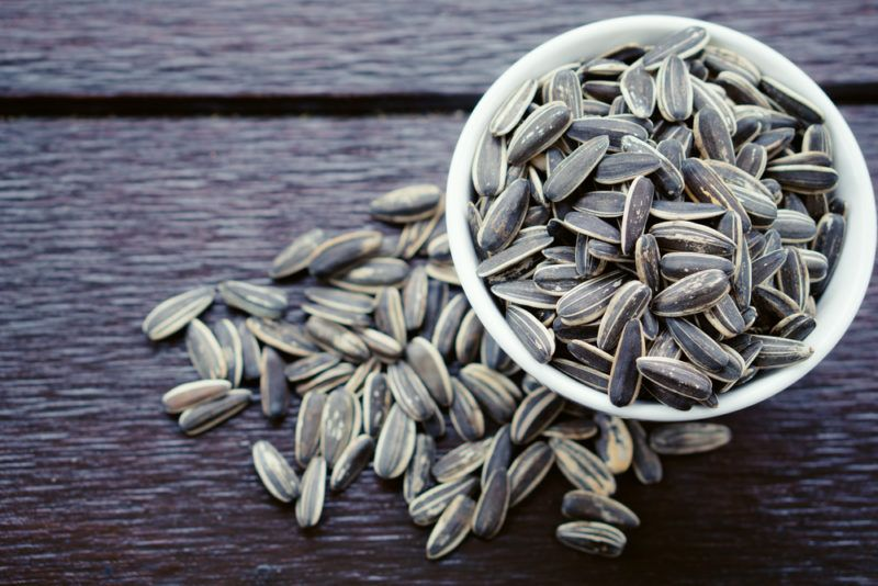 A white bowl filled with sunflower seeds, with more seeds below it on a dark wooden table