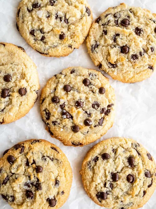 Six chocolate chip cookies on parchment paper