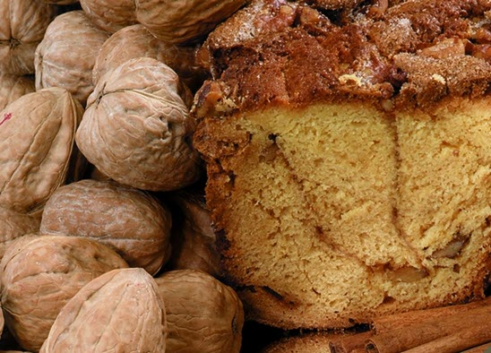 A cake next to a collection of walnuts