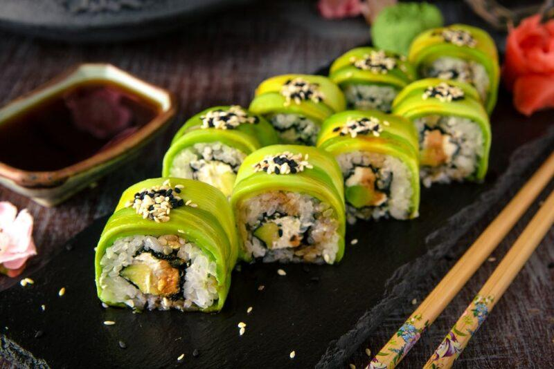A black plate with many pieces of green wrapped sushi