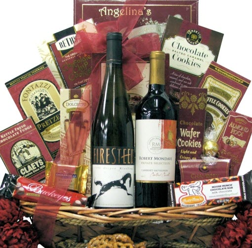 A basket containing many red-themed snacks and two bottles of wine