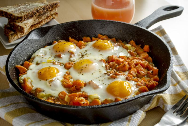 A cast iron pan with baked beans and eggs