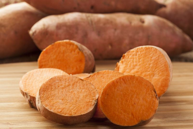 Cut sweet potatoes on a board, with whole sweet potatoes in the background