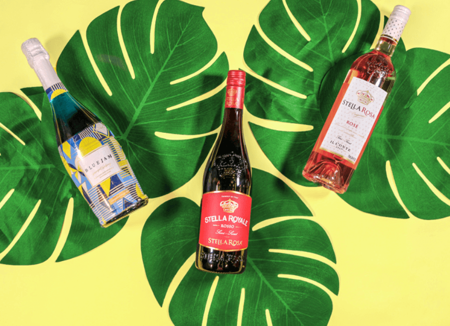 Three bottles of sweet wine laid out on giant leaves