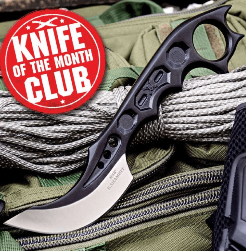 tactical knife with black handle, in the upper left corner a red circle stamp that says knife of the month club - the knife is sitting on rope and tactical bag