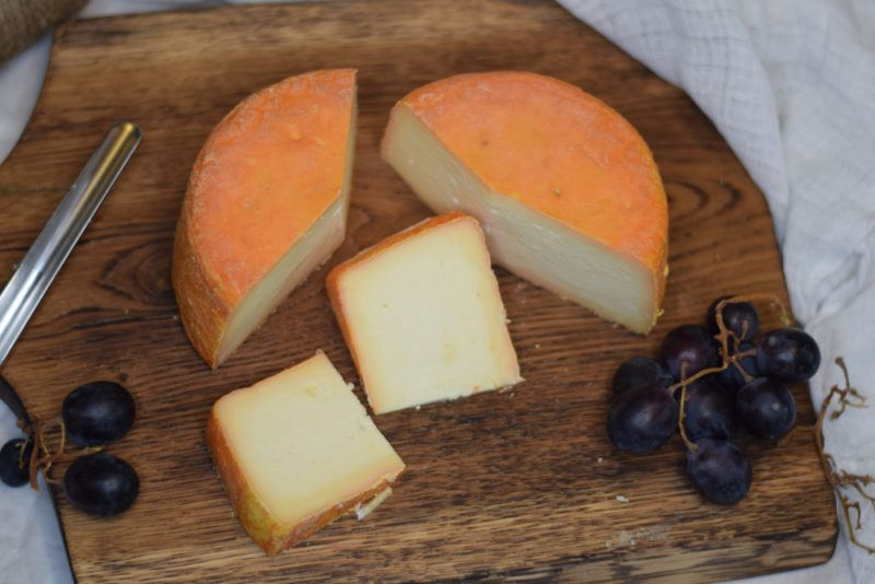 Top down image of Taleggio with grapes on a wooden board