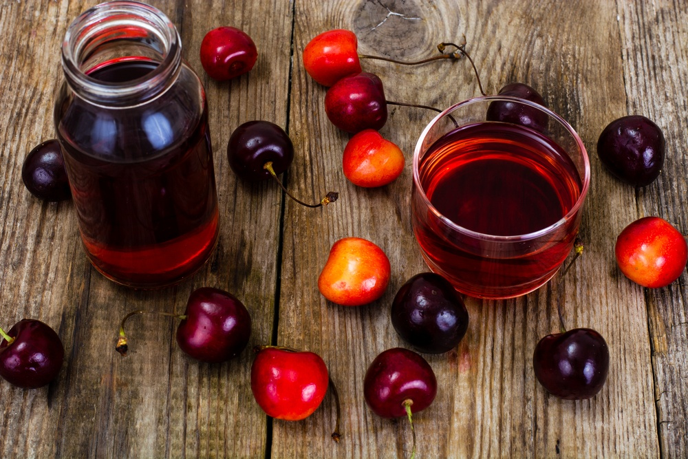 A collection of tart cherries on a table, along with a bottle and a cup of tart cherry juice