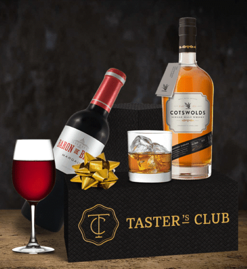 Taster's Club box with a red wine bottle and glass next to the box and a bottle of whiskey with a glass of ice with whiskey