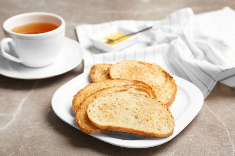 A plate of toast next to a mug of tea