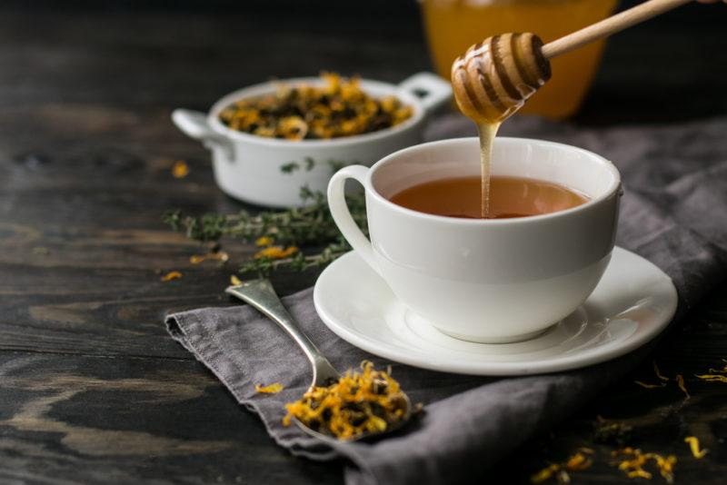 A white mug of tea with honey being added, along with a container and spoon containing herbal tea