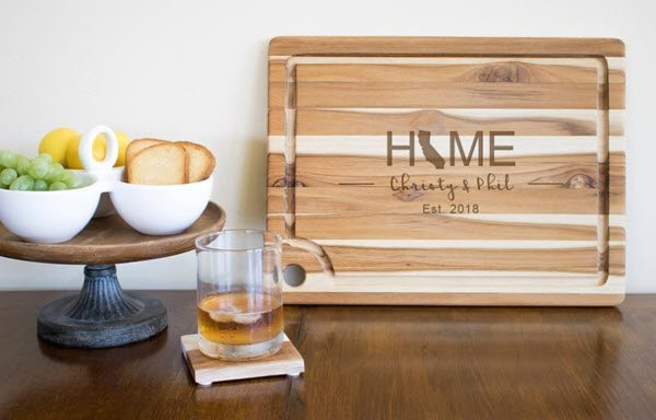 A cutting board propped up against the wall, next to a stand and a whiskey glass.