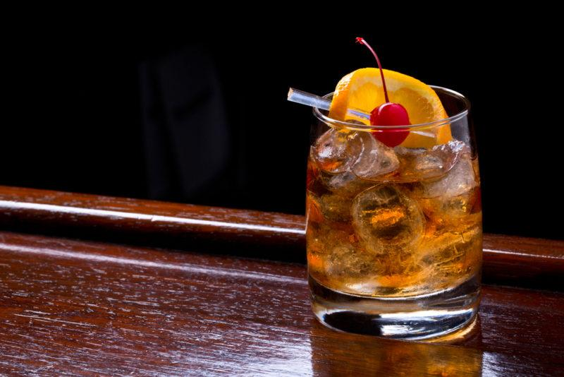 A Tequila Old Fashioned against a black background