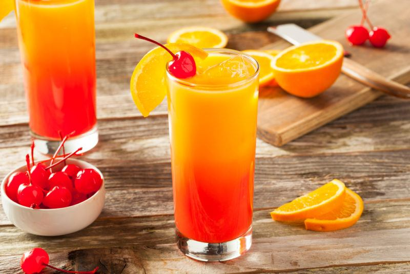 Two tequila sunrise cocktails with bing cherries and oranges