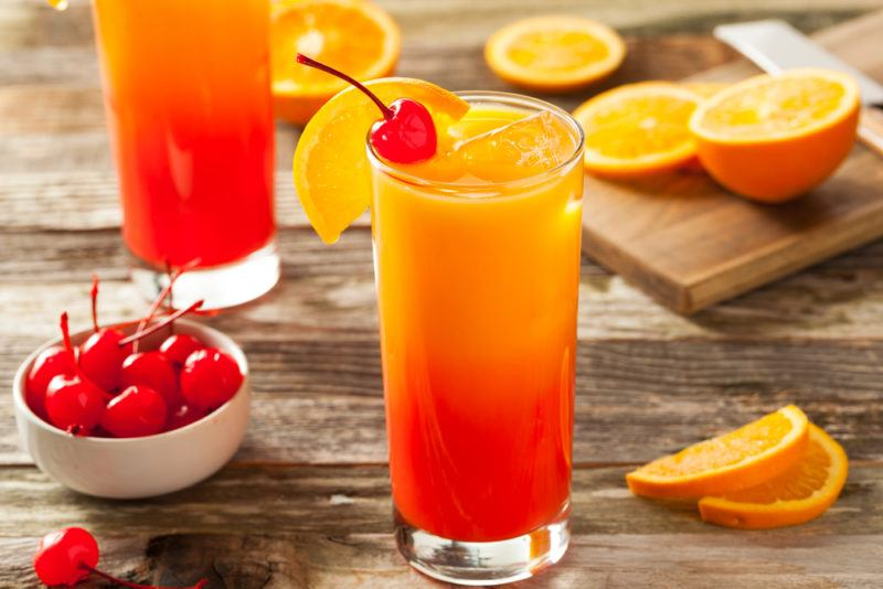 Two tequila sunrise cocktails on a table with slices of orange scattered around