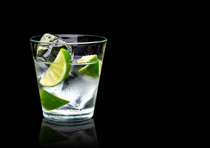 A tequila and tonic cocktail on a black background