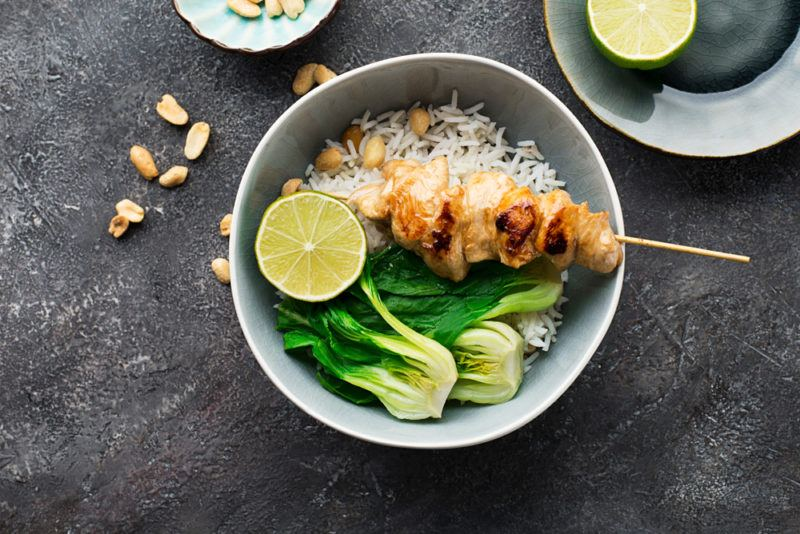 A white bowl with a chicken skewer, rice and bok choy
