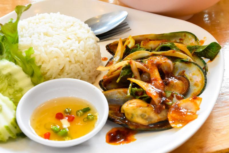 A white plate with Thai style mussels, next to rice, a spoon, veggies and dipping sauce
