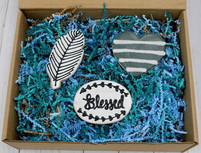 A box with blue tissue and 3 white cookies