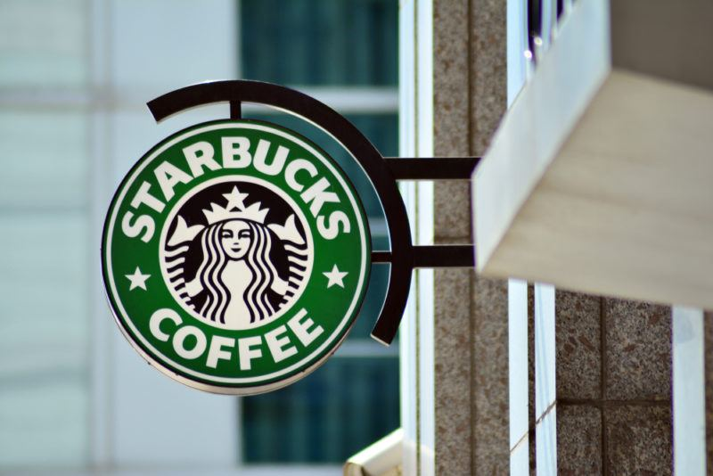The green and white Starbucks logo outside a Starbucks coffee shop