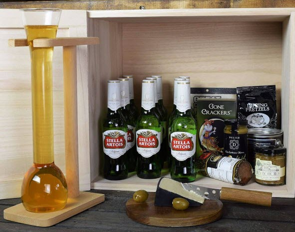 An open crate containing 9 bottles of Stella Artois and plenty of snacks. There is a full half yard beer glass next to it, along with a cutting board, cheese and olives.